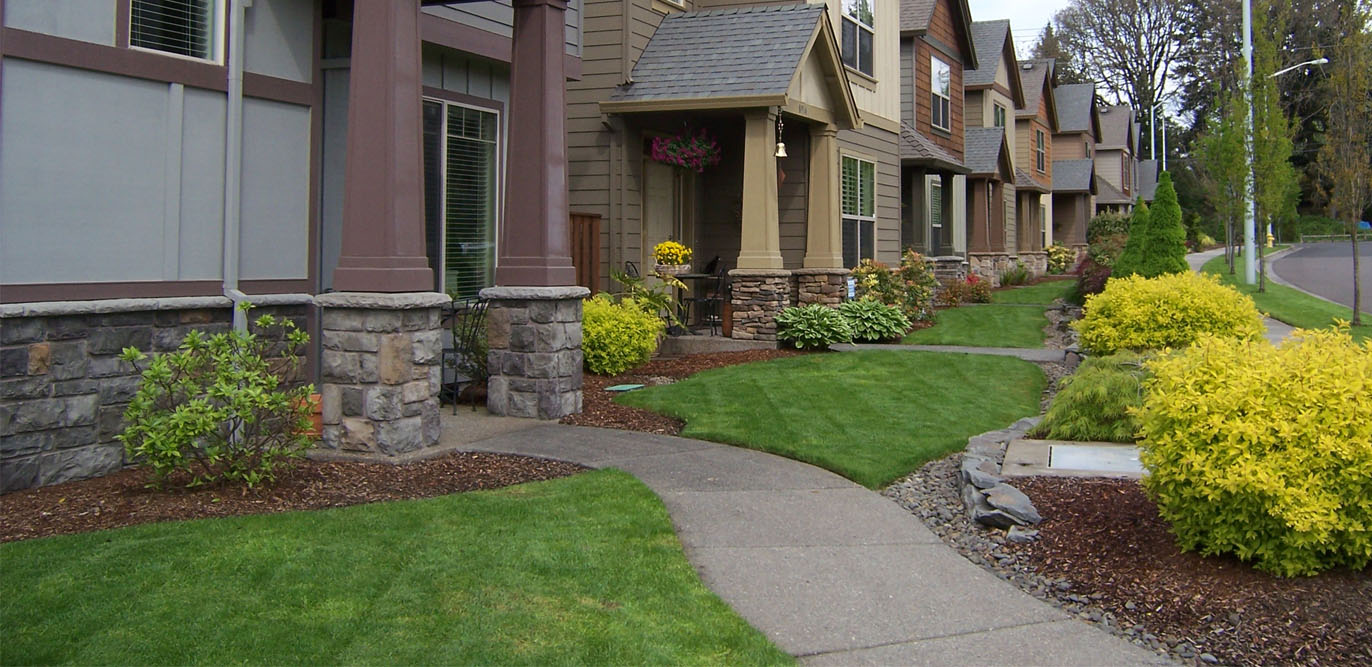 Groomed lawn, trimmed bushes, and rock